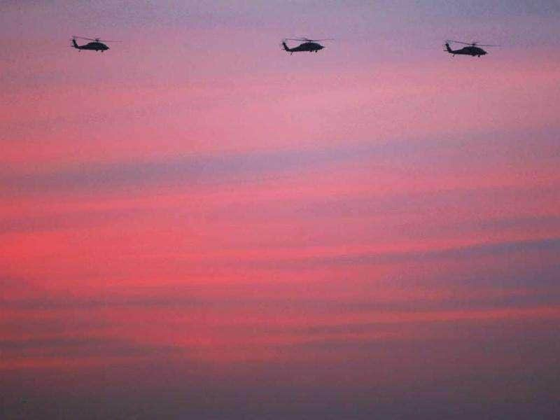 US military helicopters fly above the city at dusk. Getty Images