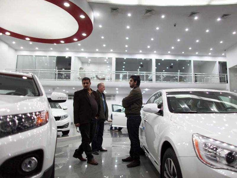 Car salesman, Aysar Hasan (R) shows cars to prospective buyers on the sales floor of the new Kia showroom that opened four months ago. Getty Images