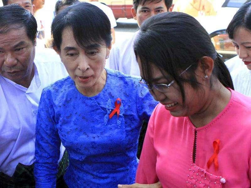 Opposition leader and Nobel peace laureate, Aung San Suu Kyi, center, and Phyu Phyu Thin, well-known AIDS activists, right, arrive at the National League for Democracy (NLD) party's headquarters to attend an event to mark World AIDS Day cerebration in Yangon, Myanmar. (AP Photo/Khin Maung Win)