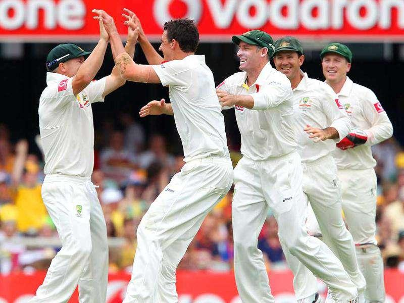 Australia's Mitchell Starc, second left, celebrates with team member David Warner, left, after getting the wicket of New Zealand's Brendon McCullum during the 1st day of their first cricket Test at the Gabba in Brisbane, Australia.