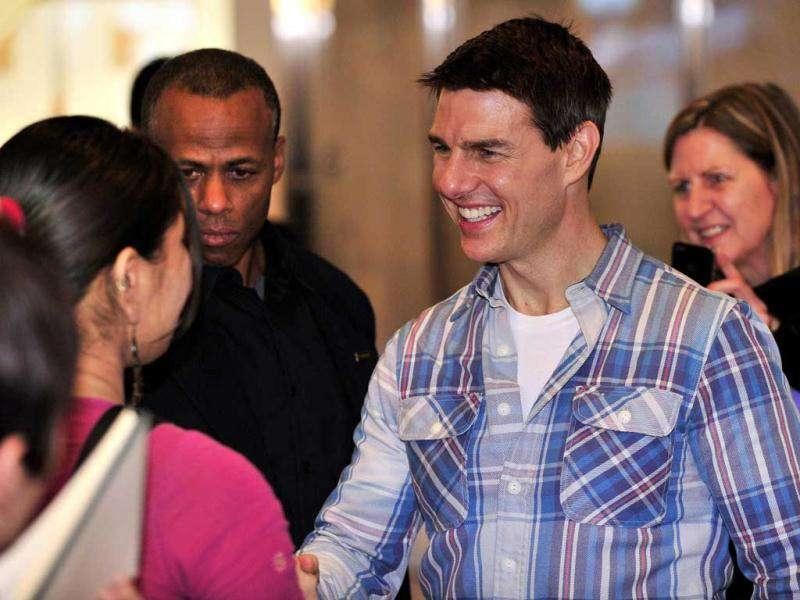 Tom Cruise greets Japanese fans upon his arrival at Tokyo's Haneda airport on November 30, 2011. (AFP)