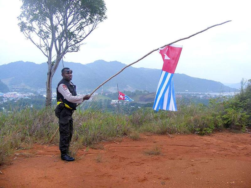 An Indonesian policeman takes down the banned Morning Star flag raised by Papuan demonstrators in Jayapura. In nearby Timika police backed by troops broke up separatist flag-raising ceremony displaying the banned Morning Star flag on the 50th anniversary of the region's claim to independence in eastern Indonesia's restive region of Papua.