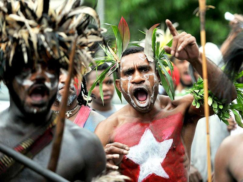 Papuan protesters, displaying the banned Morning Star flag, at a rally marking the 50th anniversary of the region's claim to independence in eastern Indonesia's restive region of Papua. Displaying separatist symbols such as the Morning Star is considered an act of treason in Indonesia and several perpetrators are serving 20-year jail terms for the offence.