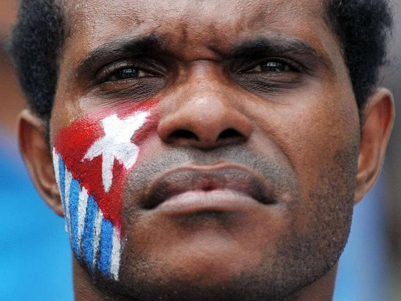 A Papuan protester with his cheek displaying the banned Morning Star flag at a demonstration in Jakarta. Displaying separatist symbols such as the Morning Star is considered an act of treason in Indonesia under the criminal code and several perpetrators are serving 20-year jail terms for the offence.