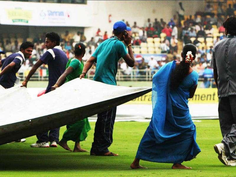 Groundsmen pull covers as it rained before the 2nd ODI between India and West Indies, at Dr YS Rajasekhara Reddy Cricket Stadium.