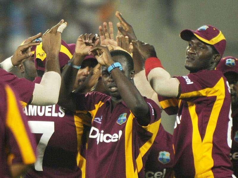West Indies cricketer Kemar Roach (C) celebrate with teammates after taking the wicket of Indian cricketer Parthiv Patel during the second One Day International (ODI) match between India and the West Indies at The YS Rajasekhara Reddy cricket stadium in Visakhapatnam. (AFP Photo)