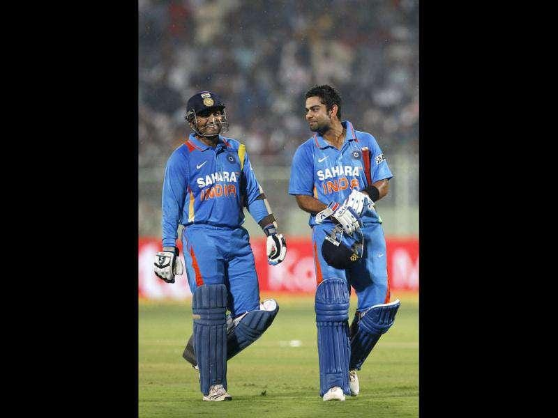 India's captain Virender Sehwag, left, and teammate Virat Kohli leave the ground after rain stopped play during their second one day international cricket match against West Indies' in Visakhapatnam. (AP Photo)