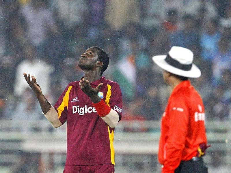 West Indies' captain Darren Sammy, left, gestures to the umpire after rain stopped play during their second one day international cricket match against India in Visakhapatnam. (AP Photo)