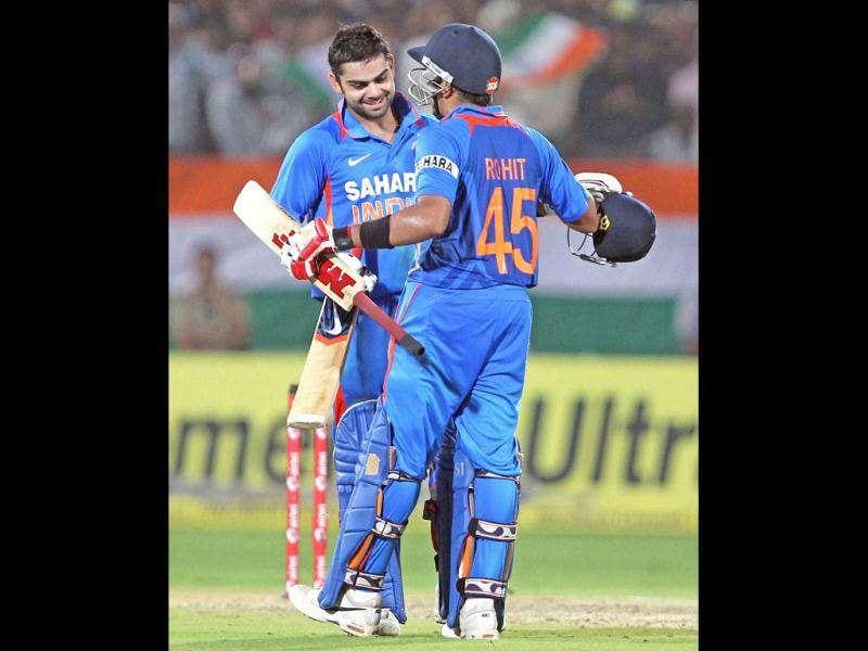 India's Rohit Sharma congratulates his teammate Virat Kohli after Kohli scored a century against West Indies during their 2nd ODI cricket match in Visakhapatnam. (PTI Photo)