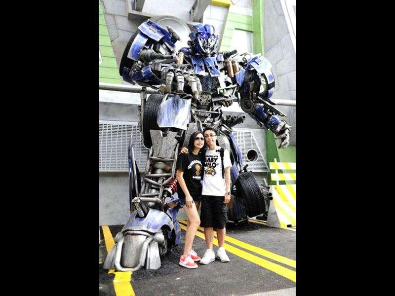 A couple poses beside a with a Transformers robot on the launch day of the new amusement park ride at Universal Studios Singapore. Transformers: The Ride is based on the Transformers movie franchise directed by Michael Bay.