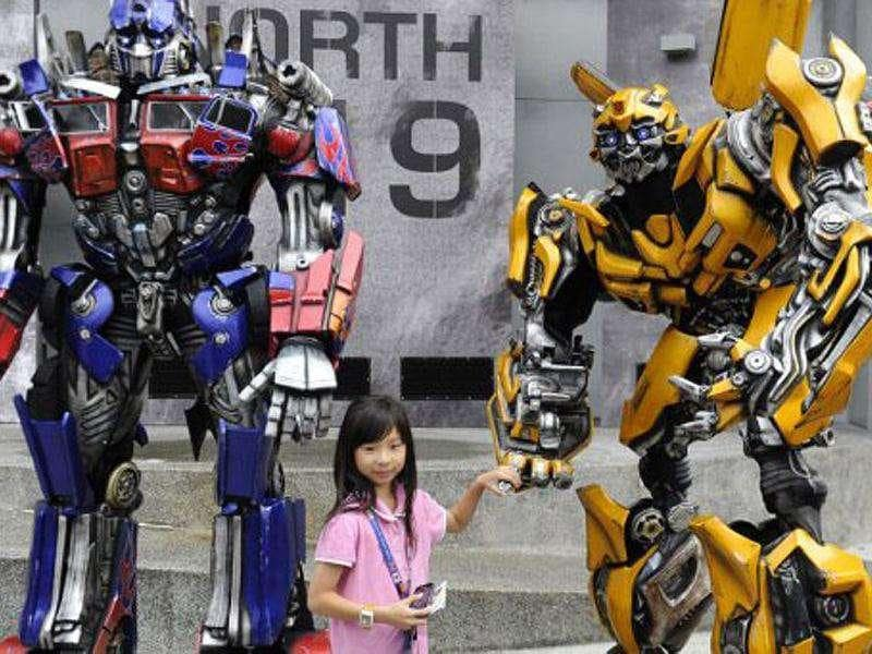 A girl poses with two Transformers robot on the launch day of the new amusement park ride at Universal Studios Singapore. Transformers: The Ride is based on the Transformers movie franchise directed by Michael Bay.