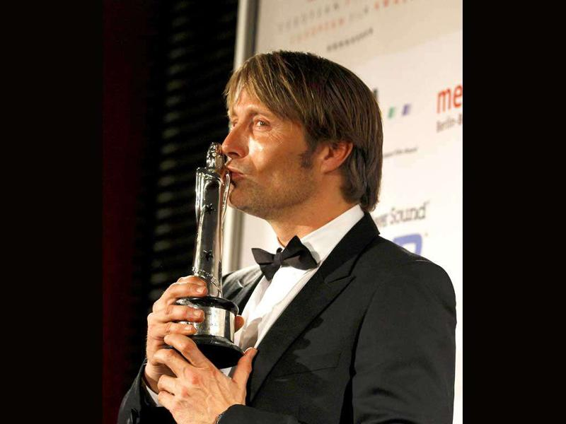 Danish actor Mads Mikkelsen poses backstage with his European Achievment in World Cinema 2011prize after the 24th European Film Awards ceremony in Berlin.