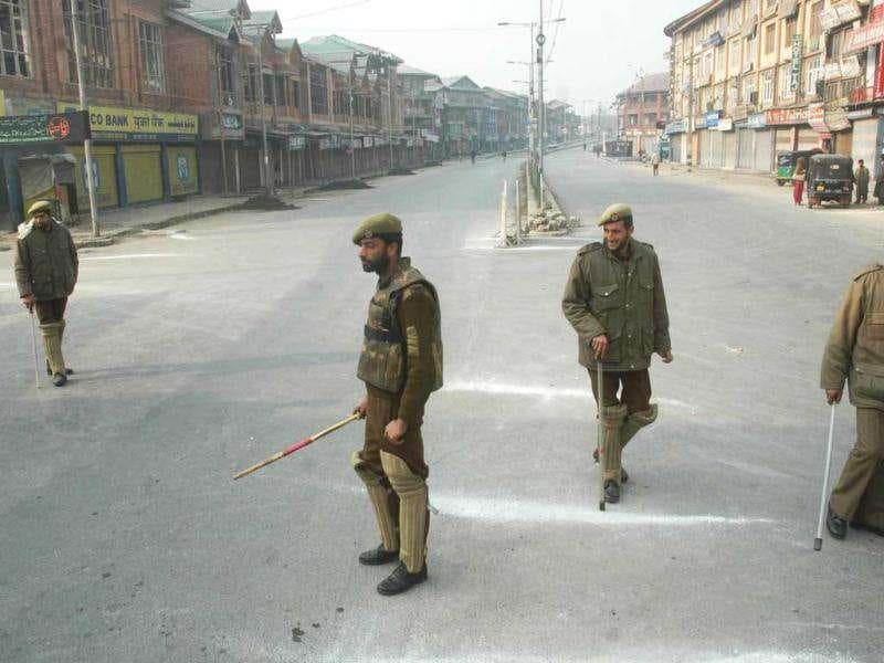 Security personnels holding sticks on their hands enforcing curfew restrictions at Budshah chowk Srinagar on Sunday as the curfew was imposed in parts of Srinagar, including Lal Chowk, to prevent Muharram procession.