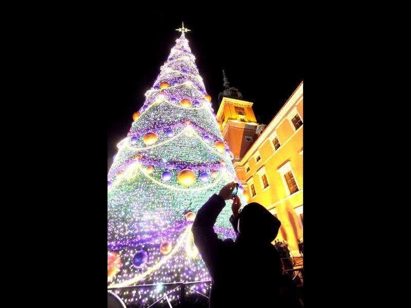 A man is silhouetted as he takes a photo of the just lit Christmas Tree in front of the Royal Castle in Warsaw, Poland, Saturday. AP