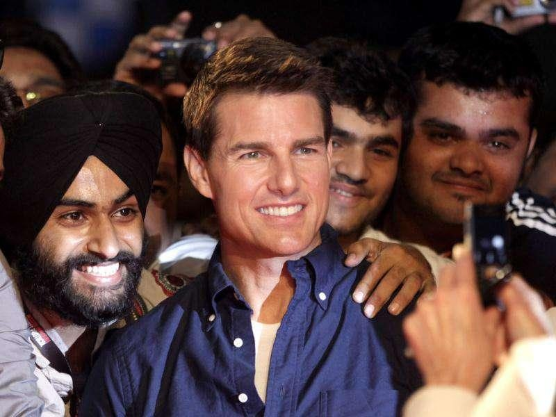 Tom Cruise poses with fans as he arrives for a special screening of his film Mission Impossible: Ghost Protocol in Mumbai.AP/Rajanish Kakade