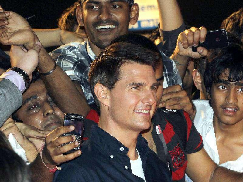 Tom Cruise looks more than happy to pose with fans as he arrives for a special screening of his film Mission Impossible: Ghost Protocol in Mumbai. AP/Rajanish Kakade