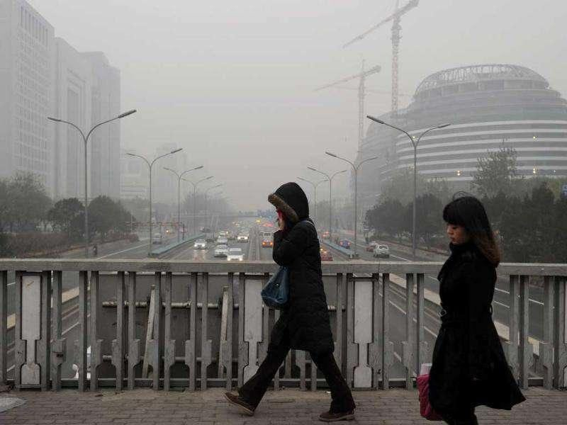 Pedestrians cross the second ring road as pollution reaches what the US Embassy monitoring station says are