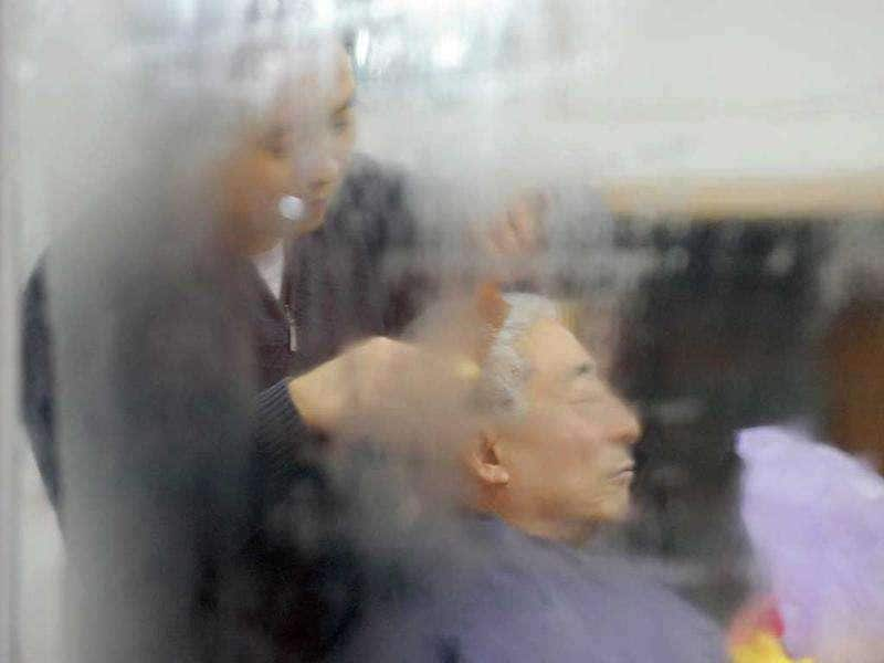 A man gets a haircut next to the window of a barber shop in Beijing. China's top climate negotiator Xie Zhenhua laid out conditions under which Beijing would accept a legally-binding climate deal that would go into force after 2020, when current voluntary pledges run out.