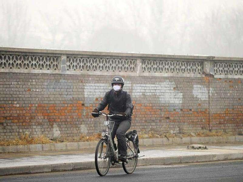 A resident rides a bicycle along a street in the haze in Beijing. The choking air that regularly descended on the Chinese capital in October and November has given fresh impetus to a growing public debate over air quality in the city, whose 20 million residents are increasingly worried.