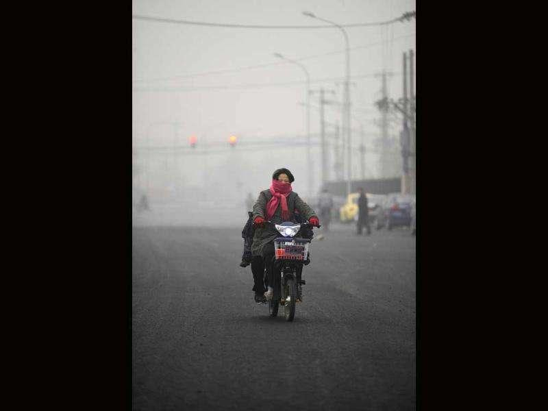 A resident rides a motorbike along a street in the haze in Beijing. The choking air that regularly descended on the Chinese capital in October and November has given fresh impetus to a growing public debate over air quality in the city, whose 20 million residents are increasingly worried.