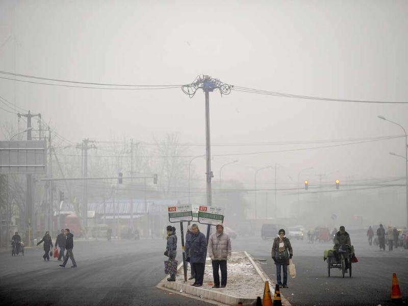 Commuters wait for public buses along a street in the haze in Beijing. The choking air that regularly descended on the Chinese capital in October and November has given fresh impetus to a growing public debate over air quality in the city, whose 20 million residents are increasingly worried.