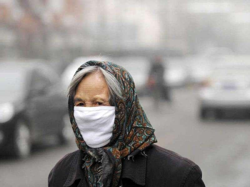 An elderly woman wearing a face mask walks along a street in the haze in Beijing. The choking air that regularly descended on the Chinese capital in October and November has given fresh impetus to a growing public debate over air quality in the city, whose 20 million residents are increasingly worried.