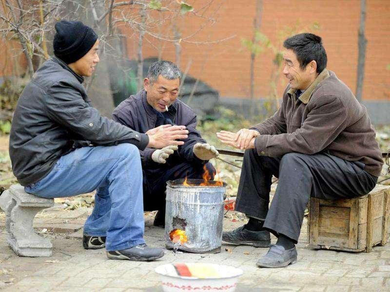 Three migrant workers stay warm with a stove fire along a street in Beijing. China's top climate negotiator Xie Zhenhua laid out conditions under which Beijing would accept a legally-binding climate deal that would go into force after 2020, when current voluntary pledges run out.