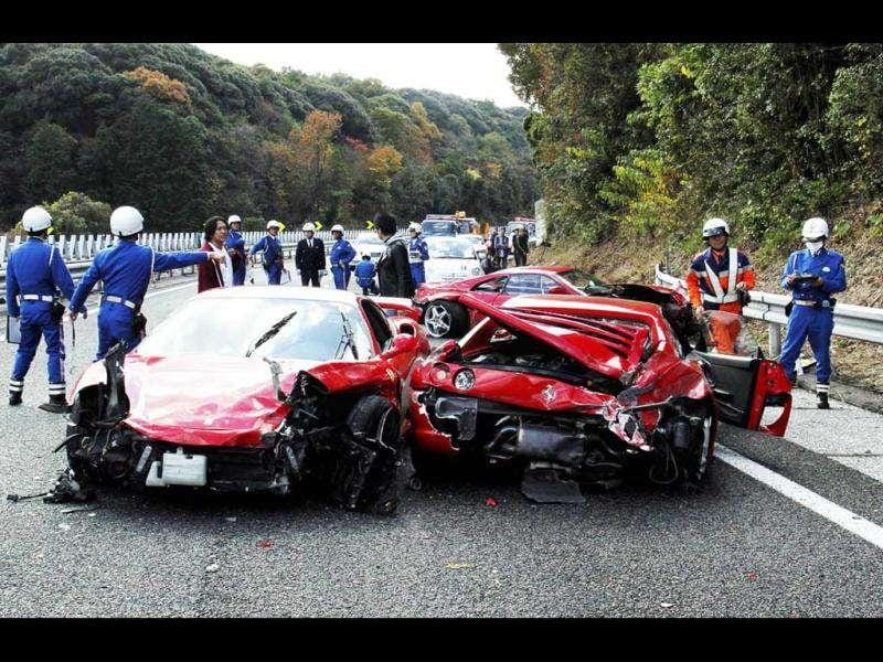 Police officers inspecting damaged Ferrari sports cars on the Chugoku highway in Shimonoseki, Yamaguchi prefecture, western Japan following a 14-vehicle pile up. AFP Photo/Yomiuri Shimbun