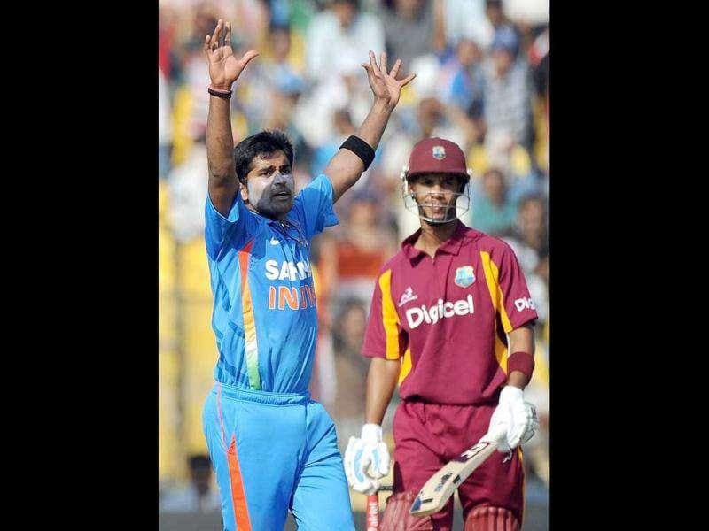 Vinay Kumar (L) celebrates the wicket of West Indies batsman Lendl Simmons (R)during the third one-day international cricket match between India and West Indies at Sardar Patel Stadium, Motera in Ahmedabad.