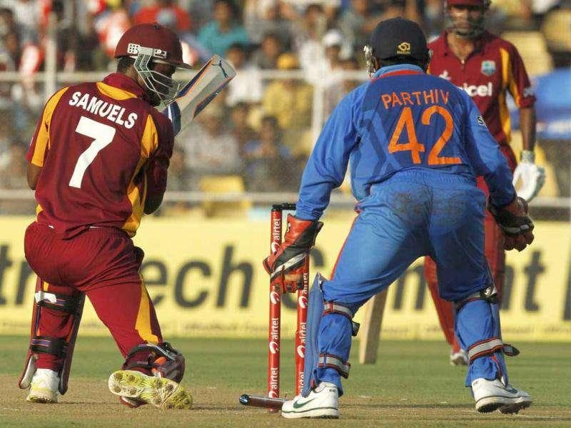 West Indies' batsman Marlon Samuels (L) looks back at his stumps after being bowled by India's Ravichandran Ashwin during their third ODI cricket match in Ahmedabad.