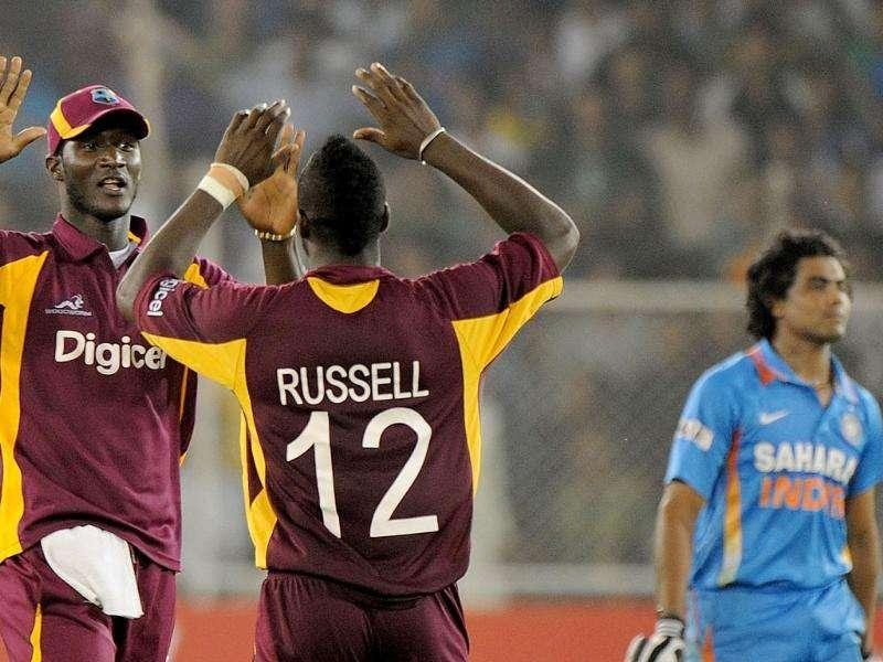 West Indies captain Darren Sammy (L) celebrates with teammate Andre Russell the wicket of Ravindra Jadeja (R) during their third one-day international cricket matchat The Sardar Patel Stadium, Motera in Ahmedabad. AFP Photo/Punit Paranjpe