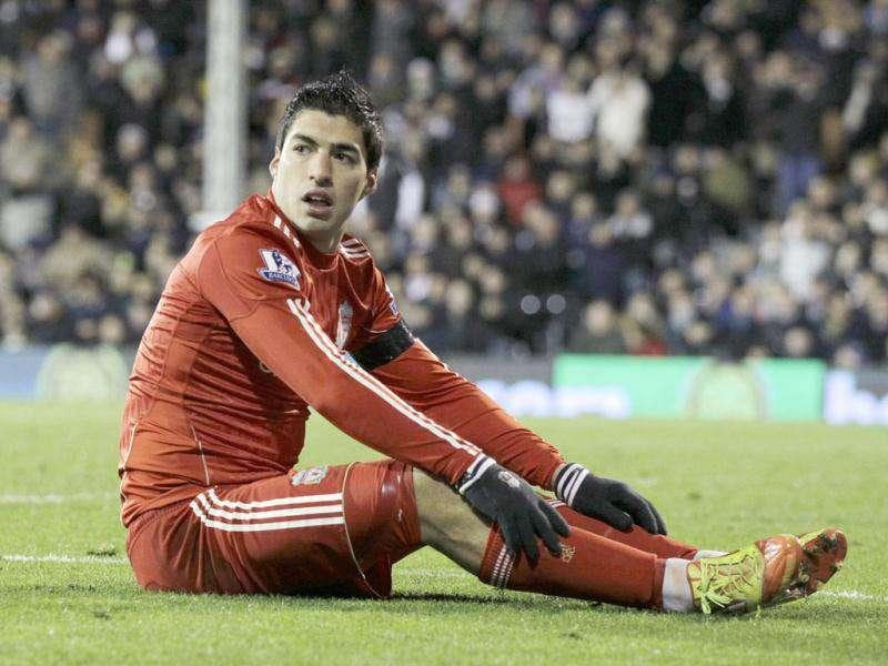 Liverpool's Luis Suarez sits in the Fulham box after a chance during the English Premier League soccer match between Fulham and Liverpool at Craven Cottage stadium in London. AP Photo/Matt Dunham