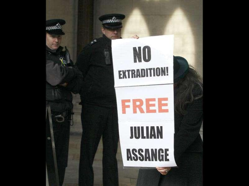 A supporter of Julian Assange, founder of WikiLeaks holds up a poster as they demonstrate at the High Court in London. A British court Monday gave WikiLeaks founder Julian Assange permission to continue his legal battle to avoid extradition to Sweden over sex crimes allegations. AP Photo/Kirsty Wigglesworth