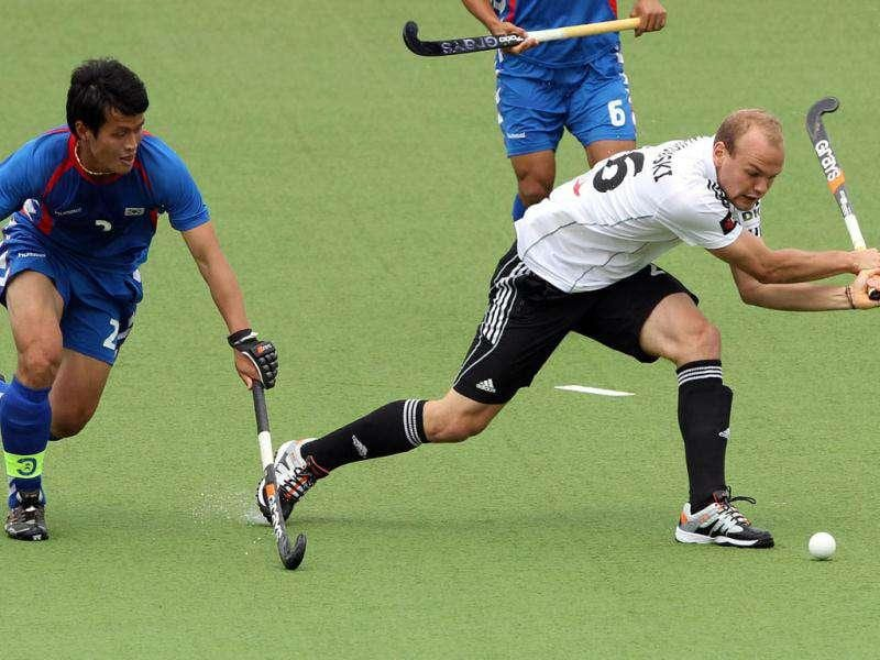 Thilo Stralkowski (R) of Germany competes with Cha Jong-Bok (L) of South Korea during their third round match of the men's hockey Champions Trophy in Auckland. Germany and South Korea drew 3-3. AFP Photo/Michael Bradley