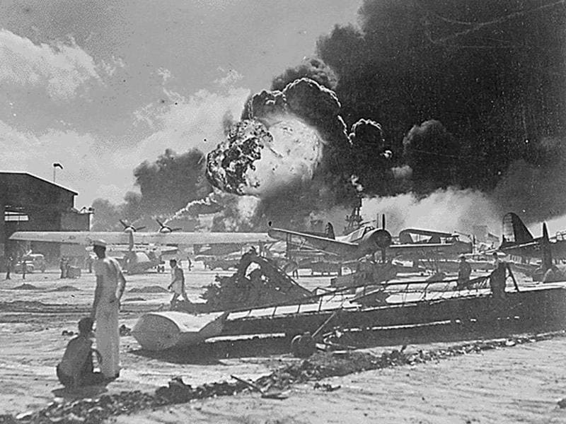 Members of the US Military stand near airplane wreckage during the surprise Japanese aerial attack at Naval Air Station at Pearl Harbor in Hawaii December 7, 1941.