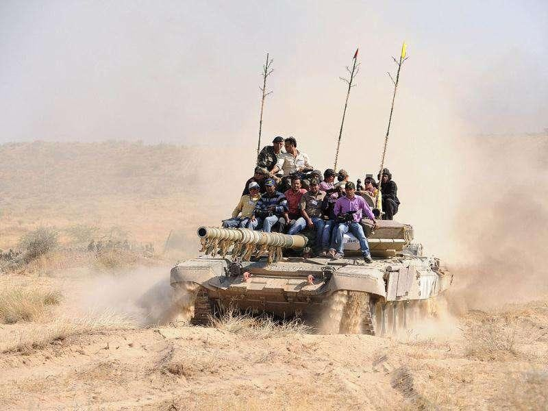 Media representatives ride on an Indian Army battle tank after the Indian Army's exercise Sudarshan Shakti in Barmer, Rajasthan. Exercise Sudarshan Shakti displayed maneuvers by mechanised forces and other components on their ability in the air and on land.