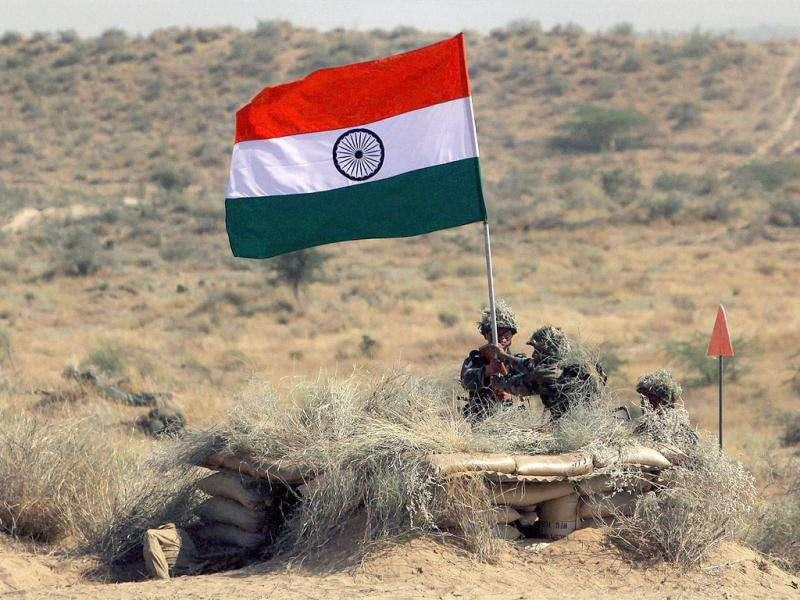 Army jawans hold a Tricolor during the Indian Army exercise Sudarshan Shakti at Bugundi battle field near Barmer in Rajasthan.