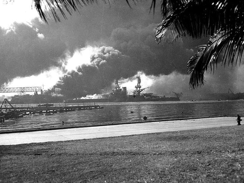 USS Nevada is seen ablaze off the Ford Island seaplane base, with her bow pointed up-channel during the Japanese attack on Pearl Harbor, Hawaii on December 7, 1941.