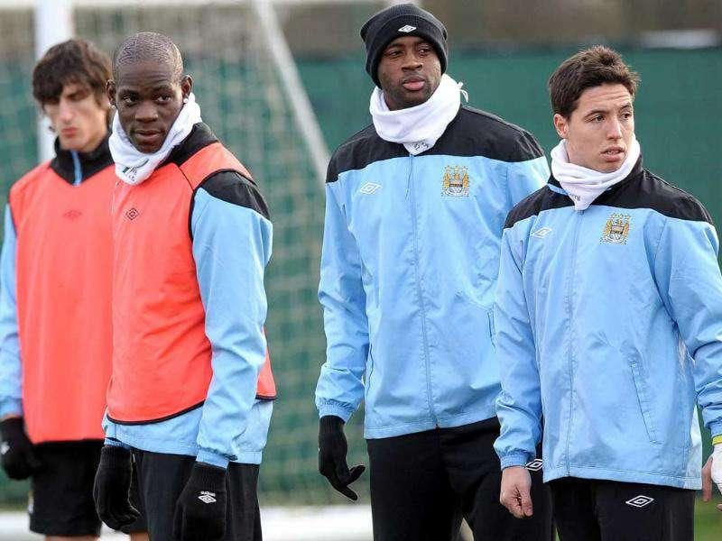 Manchester City forward Mario Balotelli (2L), defender Yaya Toure (2R) and midfielder Samir Nasri (R) arrive for a training session in Manchester. AFP Photo/Paul Ellis