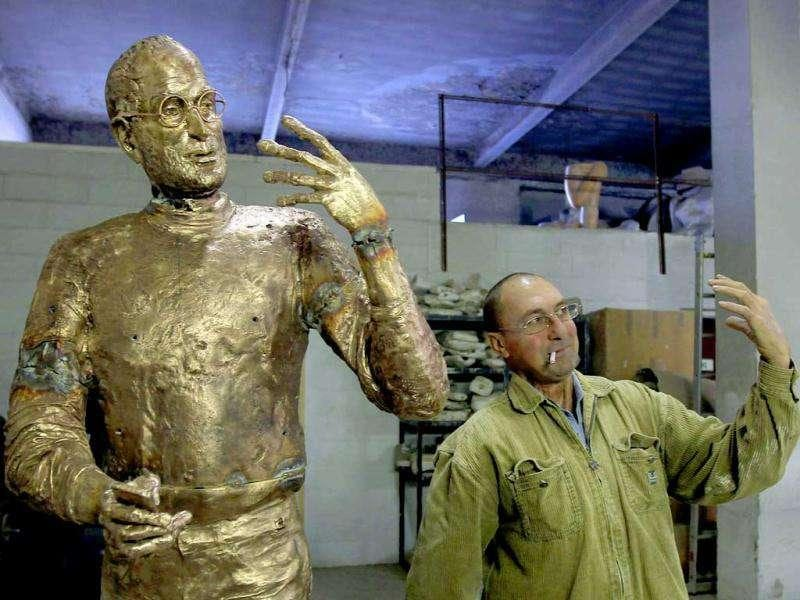 An assistant to Hungarian sculptor Erno Toth mimics the pose of the sculptor's latest work, a bronze statue of late Apple co-founder Steve Jobs, in Budapest. Reuters/Laszlo Balogh