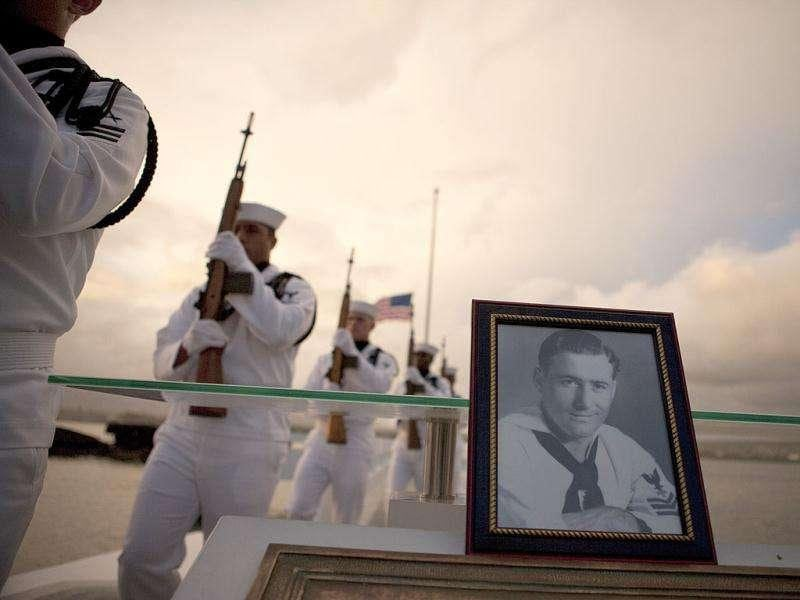 Navy Region Hawaii Honor Guard march past a photograph of Pearl Harbor survivor Lee Soucy during the internment ceremony for Soucy in Honolulu. Soucy, who died last year at the age of 90, wanted to have his ashes interred inside the USS Utah, his ship that sank during the surprise Japanese attack on Pearl Harbor in Dec. 7, 1941.