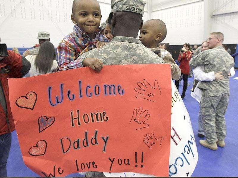 US Army Pfc. Keither Singleton holds his sons Keither Jr., 3, left, and Shamari, 2, right, after he returned home to Joint Base Lewis McChord in Washington state along with other soldiers who had been serving in Iraq.