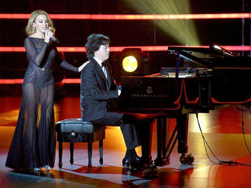 Australian singer Kylie Minogue performs with Chinese pianist Yundi Li on the stage during the 2011 Elite Model Look contest held in Shanghai.