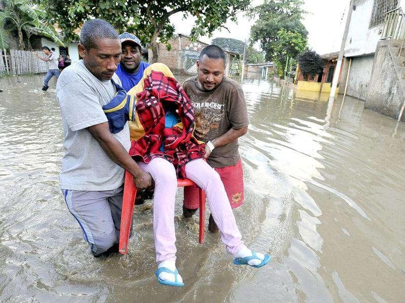 Men carry a sick woman through a flooded street in northern Cali, Colombia. An extended rainy season has caused devastating floods and widespread damage in the country for the second year in a row. Meteorologist blame the intense rains on La Nina weather phenomenon which occurs in the Pacific Ocean.