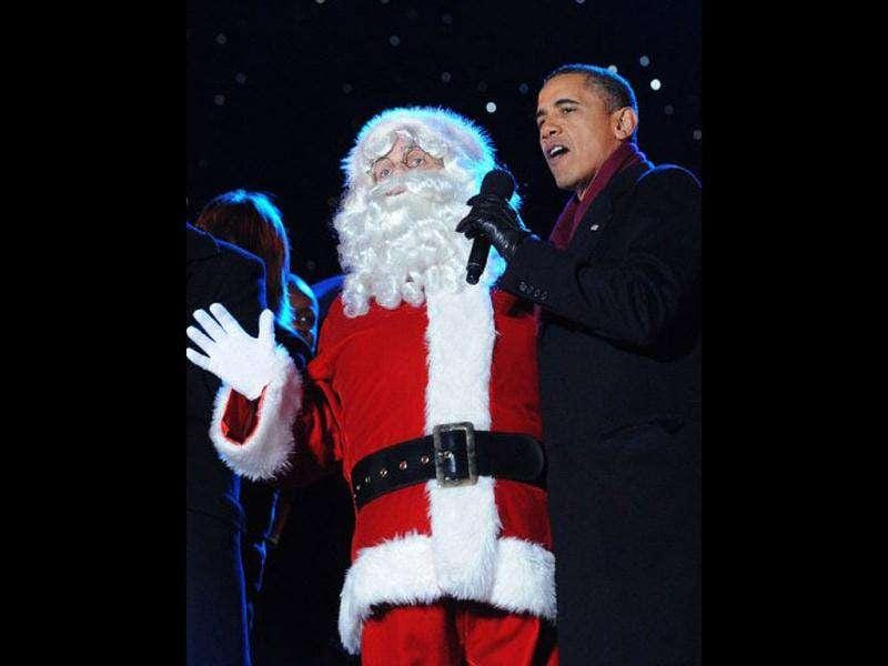 A man dressed as Santa Claus sings with US President Barack Obama during the finale fo the annual lighting of the National Christmas tree at The Ellipse in Washington, DC.