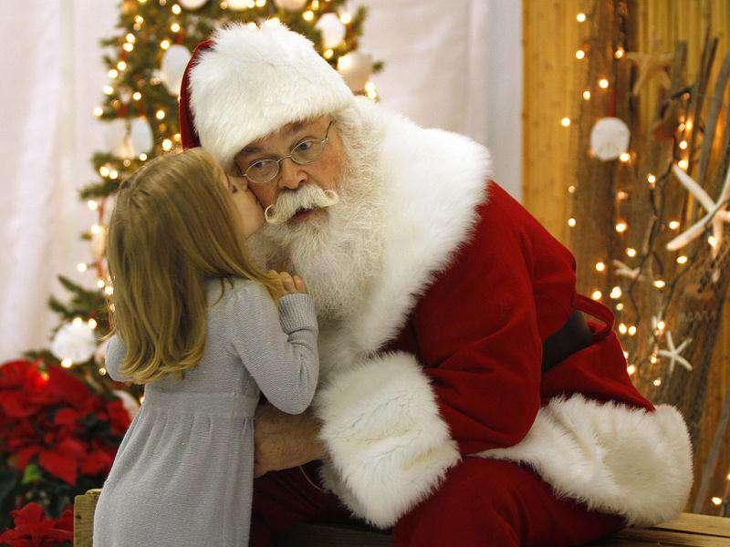 Santa Claus Cliff Snider, gets a kiss on the cheek from Bella Champion, 3, during a Christmas photo shoot at the