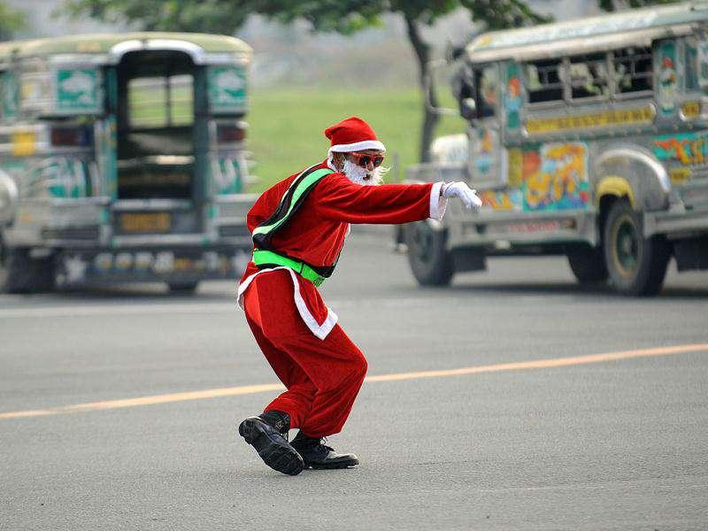 Philippine traffic enforcer Ramiro Hinojas, dressed as Santa Claus costume, directs traffic along a major road in Manila.