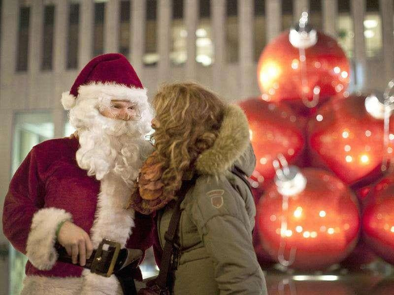 A man dressed as Santa Claus speaks to a woman on West 49th Street in New York.
