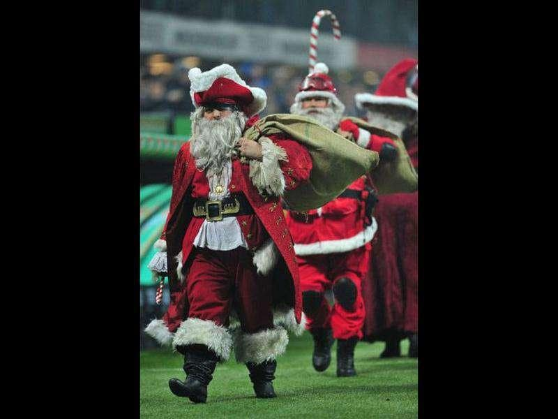 People dressed as Santa Claus walk on the pitch prior the Italian Serie A football match between AC Milan and Chievo at San Siro Stadium in Milan.