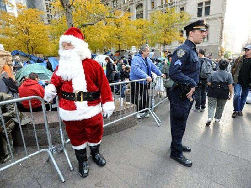 A man dressed as a Santa Claus (L) stands on the sidewalk near a New York Police Department officer (R) as demonstrators with 'Occupy Wall Street' continue their protest at Zuccotti Park.